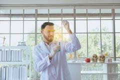 Άτομα επιστημόνων που εργάζονται βάζοντας το ιατρικό δείγμα χημικών ουσιών στο σωλήνα δοκιμής στο εργαστήριο στοκ φωτογραφίες