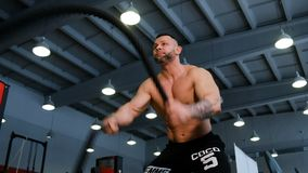 Άτομο ικανότητας που κάνει το έντονο workout που χρησιμοποιεί την πρόκληση άσκησης σχοινιών μάχης στον ισχυρό μυϊκό αθλητικό τύπο απόθεμα βίντεο