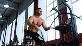 Άτομο ικανότητας που κάνει το έντονο workout που χρησιμοποιεί την πρόκληση άσκησης σχοινιών μάχης στον ισχυρό μυϊκό αθλητικό τύπο φιλμ μικρού μήκους
