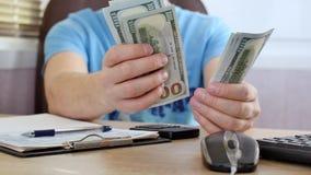 Άτομο με τα μπλε μετρώντας δολάρια μπλουζών και γεμίζοντας φορολογική μορφή απόθεμα βίντεο