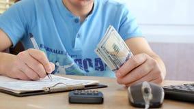 Άτομο με τα μπλε μετρώντας δολάρια μπλουζών και γεμίζοντας φορολογική μορφή φιλμ μικρού μήκους