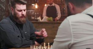 Άτομο με τη γενειάδα που εξετάζει τον πίνακα σκακιού και το ουίσκυ κατανάλωσης φιλμ μικρού μήκους