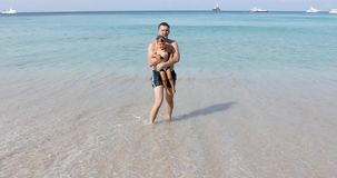 Άτομο με το περπάτημα αγοριών στην ακτή απόθεμα βίντεο