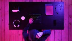 Άτομο στα γυαλιά που παίζει ένα παιχνίδι στο lap-top στοκ φωτογραφία