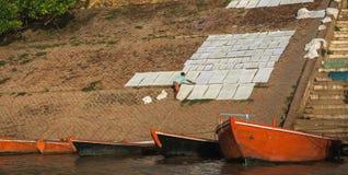 Άτομο στην πλάτη του που τείνει τα ενδύματα στις όχθεις του ποταμού του Γάγκη, δίπλα στις βάρκες, στο Varanasi, Ινδία στοκ εικόνες