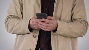 Άτομο στο παλτό τάφρων που χρησιμοποιεί το κινητό έξυπνο τηλέφωνο στο υπόβαθρο κλίσης απόθεμα βίντεο