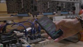 Άτομο τεχνικών που παρουσιάζει πρόοδο λογισμικού μεταλλείας στην επίδειξη smartphone κοντά στην εγκατάσταση γεώτρησης μεταλλείας  απόθεμα βίντεο
