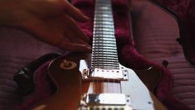 Άτομο που βγάζει μια κιθάρα από την περίπτωση closeup απόθεμα βίντεο