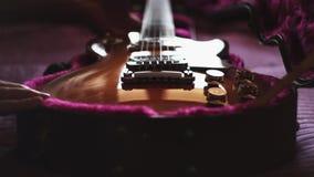 Άτομο που βγάζει μια κιθάρα από την περίπτωση closeup φιλμ μικρού μήκους