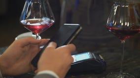 Άτομο που κάνει την πληρωμή μέσω της τεχνολογίας NFC στο κινητό τηλέφωνο στον καφέ απόθεμα βίντεο