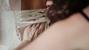 Άτομο που δένει έναν κορσέ στο γαμήλιο φόρεμα νυφών ` s απόθεμα βίντεο