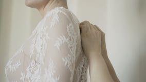 Άτομο που δένει έναν κορσέ στο γαμήλιο φόρεμα νυφών ` s φιλμ μικρού μήκους