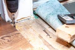 Άτομο που χρησιμοποιεί τη μηχανή τρυπανιών εγκαθιστώντας το νέο ξύλινο φυλλόμορφο δάπεδο στο σπίτι στοκ εικόνες με δικαίωμα ελεύθερης χρήσης