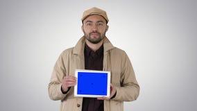 Άτομο που περπατά και που κρατά την ταμπλέτα με το μπλε πρότυπο οθόνης στο υπόβαθρο κλίσης απόθεμα βίντεο