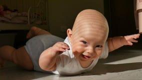 Άτριχο μικρό παιδί που βρίσκεται στο πάτωμα και που εξετάζει τη κάμερα με το toothyless χαμόγελο απόθεμα βίντεο