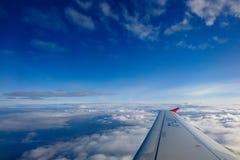 Άποψη από το φωτιστικό αεροπλάνων Η άποψη από το παράθυρο του αεροπλάνου στο φτερό, τα σύννεφα και το μπλε ουρανό στοκ εικόνες