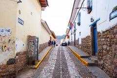 Άποψη της μακριάς οδού με τα αυτοκίνητα και τους ανθρώπους που περπατούν εμπρός σε Cusco στοκ εικόνα