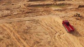 Άποψη του κενού μεγάλου κόκκινου φορτηγού που κινείται σε μια αμμώδη διαδρομή κοντά στον κίτρινο εκσκαφέα στην έρημο ή τους αμμόλ απόθεμα βίντεο