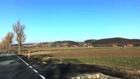 Άποψη του τομέα ενάντια σε δύο ανεμοστροβίλους και της μικρής πόλης την πρώιμη άνοιξη Άποψη από την κίνηση του αυτοκινήτου στην Π απόθεμα βίντεο