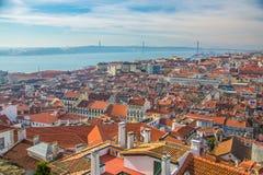 Άποψη των οδών και των πορτοκαλιών στεγών της παλαιάς πόλης Λισσαβώνα Πορτογαλία Στην απόσταση, δείτε τη γέφυρα της 25ης Απριλίου στοκ εικόνα