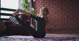 Έναρξη καλημέρας για μια κυρία που γιόγκα άσκησης πόδια τεντώματος, καθμένος στο χαλί και κάνει τις σκληρές ασκήσεις για φιλμ μικρού μήκους