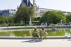 Ένας άνδρας και μια γυναίκα στηρίζονται από τη λίμνη στον κήπο Tuileries Γαλλία Παρίσι στοκ φωτογραφίες