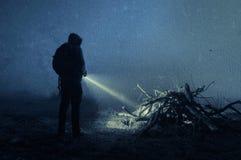 Ένας απόκοσμος με κουκούλα αριθμός με έναν φανό, που εξετάζει το μυστήριο σωρό του ξύλου Σε μια σκοτεινή, ομιχλώδη χειμερινή νύχτ στοκ φωτογραφίες με δικαίωμα ελεύθερης χρήσης