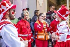 Ένας ελληνικός υπάλληλος Ερυθρών Σταυρών θηλυκών προσπαθεί να την καθαρίσει που χρωματίζεται από το πρόσωπο συμμετεχόντων παρελάσ στοκ εικόνες με δικαίωμα ελεύθερης χρήσης