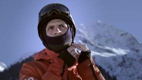 Ένας επαγγελματικός αναβάτης βάζει σε ένα κράνος ή ένα σκληρό καπέλο Να πάρει έτοιμος να κάνει σκι ή σνόουμπορντ Απολαμβάνει το χ φιλμ μικρού μήκους