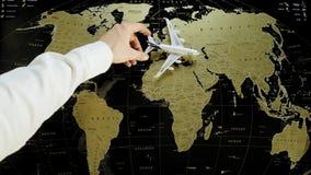 Ένας επιβάτης αεροπλάνου παιχνιδιών εδάφη στα ανθρώπινα χεριών σε έναν παγκόσμιο χάρτη απόθεμα βίντεο