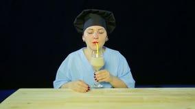 """Ένας θηλυκός αρχιμάγειρας σε ένα μαύρο υπόβαθρο δοκιμάζει έναν καταφερτζή φρούτων και παρουσιάζει """"σημάδι των κατηγοριών απόθεμα βίντεο"""
