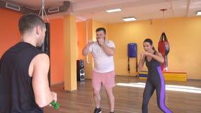 Ένας καυκάσιος αρσενικός εκπαιδευτής διδάσκει σε ένα γενειοφόρα άτομο και σε ένα κορίτσι τη σωστή διάτρηση στη πολεμική τέχνη, μό απόθεμα βίντεο