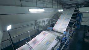 Ένας μεταφορέας κινεί τα φύλλα σε ένα γραφείο εκτύπωσης, κλείνει επάνω απόθεμα βίντεο