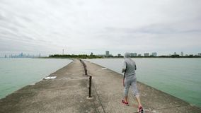 Ένας νέος αθλητής συμμετέχει στον αθλητισμό, που τρέχει κατά μήκος της προκυμαίας της λίμνης, μπροστινή πλάγια όψη καμερών φιλμ μικρού μήκους