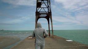 Ένας νέος αθλητής συμμετέχει στον αθλητισμό, που τρέχει κατά μήκος της προκυμαίας της λίμνης απόθεμα βίντεο
