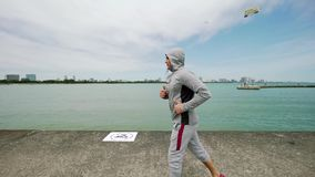 Ένας νέος αθλητής συμμετέχει στον αθλητισμό, που τρέχει κατά μήκος της προκυμαίας της λίμνης κίνηση αργή απόθεμα βίντεο