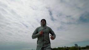Ένας νέος αθλητής συμμετέχει στον αθλητισμό, που περιορίζει κατά μήκος της προκυμαίας της λίμνης για να ολοκληρώσει την άποψη φιλμ μικρού μήκους