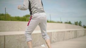 Ένας νέος αθλητικός εγκιβωτισμός τραίνων ατόμων εκτελεί εκτελεί τα άλματα στο stairson που τα σκαλοπάτια ασκούν στα πλαίσια απόθεμα βίντεο