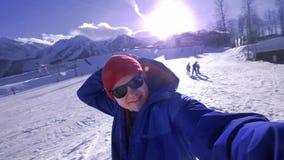 Ένας νέος τύπος εξετάζει τη κάμερα, βάζει σε μια λόγχη στο κεφάλι του Απολαμβάνει τα χειμερινά χιονοσκεπή βουνά Φθορά ενός μπλε σ απόθεμα βίντεο