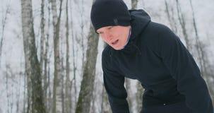 Ένας νεαρός άνδρας σε ένα σκούντημα πρωινού στο χειμερινό δάσος ήταν κουρασμένος και σταματημένος για να στηρίζεται και έτρεξε επ απόθεμα βίντεο