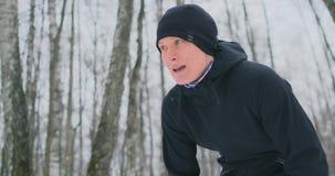 Ένας νεαρός άνδρας σε ένα σκούντημα πρωινού στο χειμερινό δάσος ήταν κουρασμένος και σταματημένος για να στηρίζεται και έτρεξε επ φιλμ μικρού μήκους