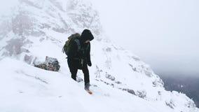 Ένας νεαρός άνδρας, ένας τουρίστας, με ένα σακίδιο πλάτης στους ώμους του ανέρχεται στην κορυφή ενός χιονισμένου βουνού απόθεμα βίντεο