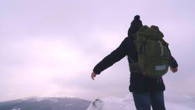 Ένας νεαρός άνδρας, ένας τουρίστας, στέκεται στην άκρη ενός χιονισμένου βουνού και θαυμάζει την κορυφή του βουνού απόθεμα βίντεο