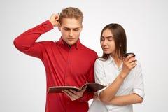 Ένας όμορφος νεαρός άνδρας σε ένα κόκκινο πουκάμισο εξετάζει το βιβλίο που γρατσουνίζει σκεπτικά το κεφάλι στοκ φωτογραφίες