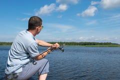 Ένας ψαράς στην τράπεζα αλιεύει σε μια περιστροφή στον ποταμό ενάντια στο μπλε ουρανό στοκ φωτογραφία με δικαίωμα ελεύθερης χρήσης