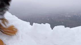 Ένας τουρίστας ατόμων πηγαίνει σε ένα χιονώδες βουνό κατά μήκος ενός επικίνδυνου απότομου βράχου απόθεμα βίντεο