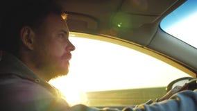Ένας τύπος με μια γενειάδα οδηγεί ήπια ένα αυτοκίνητο στον ήλιο απόθεμα βίντεο