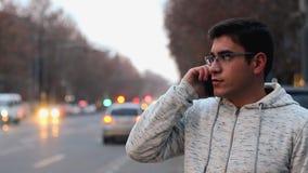 Ένας τύπος με τα γυαλιά και ένα άσπρο πουκάμισο μιλά στο τηλέφωνο και 0, σε ένα υπόβαθρο bokeh των κινούμενων προβολέων αυτοκινήτ απόθεμα βίντεο