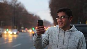 Ένας τύπος με τα γυαλιά και ένα άσπρο πουκάμισο μιλά στο skype με το μαύρο τηλέφωνο και τα γέλια, σε ένα υπόβαθρο bokeh του κινού απόθεμα βίντεο