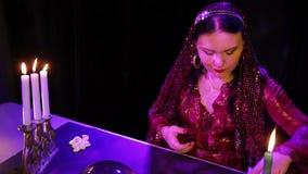 Ένας τσιγγάνος σε ένα κόκκινο φόρεμα σε ένα μαγικό σαλόνι από το φως ιστιοφόρου διαβάζει το μέλλον στις κάρτες απόθεμα βίντεο